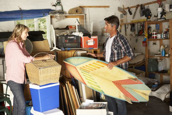 couple clearing cluttered garage
