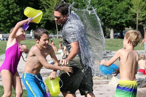 Family in park wearing swim suits and dumping pails of water on each other